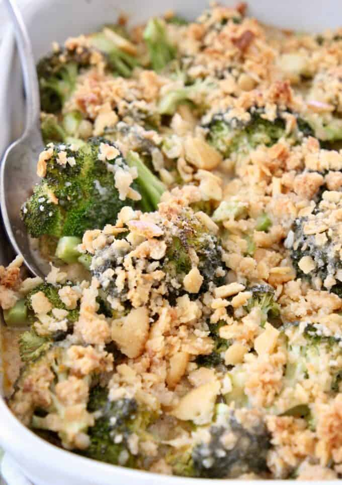 broccoli casserole topped with ritz crackers with serving spoon in the dish
