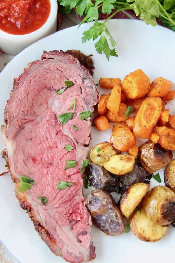 overhead image of sliced prime rib on plate with roasted vegetables