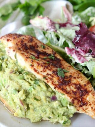 guacamole stuffed chicken on plate with salad