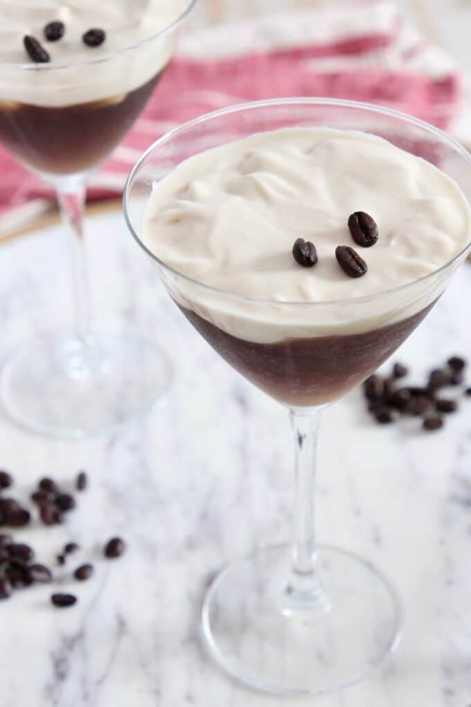 two espresso martinis in martini glasses sitting on marble serving tray