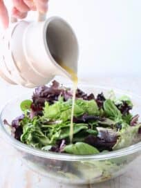 small pitcher pouring vinaigrette dressing on salad in a glass bowl