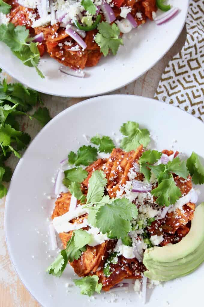 chilaquiles on white plate, topped with cilantro and avocado