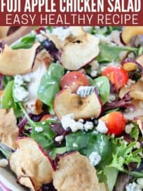 salad in bowl with apple chips and gorgonzola cheese crumbles