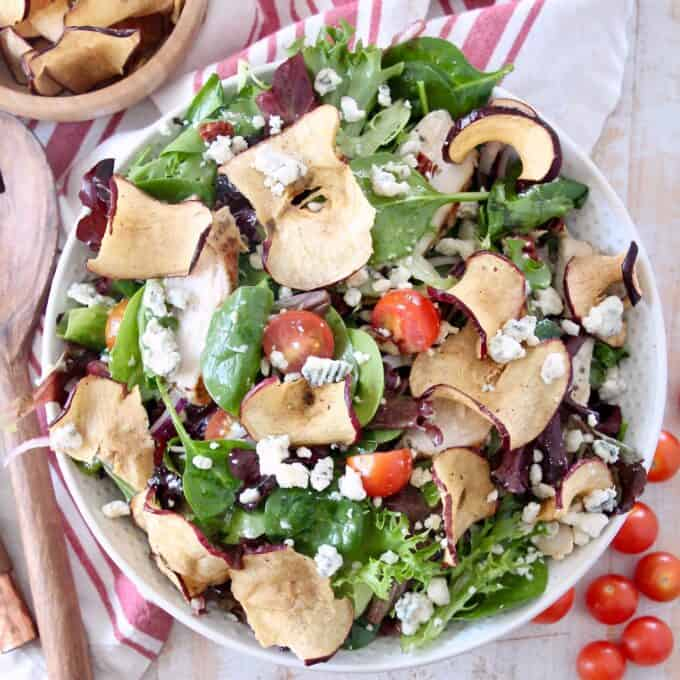 salad in bowl with apple chips and cherry tomatoes