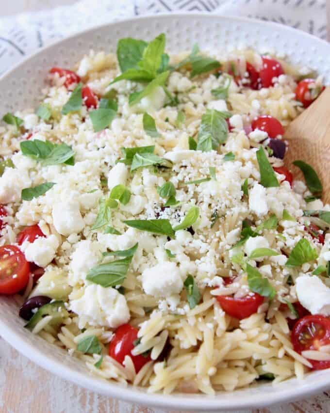 orzo pasta salad in bowl topped with fresh mint and feta cheese