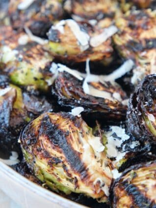 grilled brussels sprouts in bowl topped with grated parmesan cheese