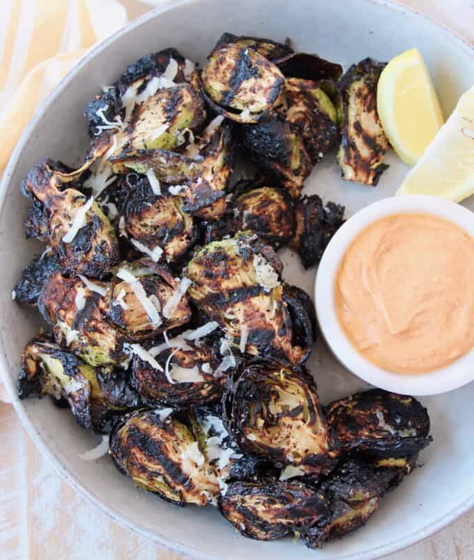 grilled brussels sprouts in bowl with harissa tahini dipping sauce on the side