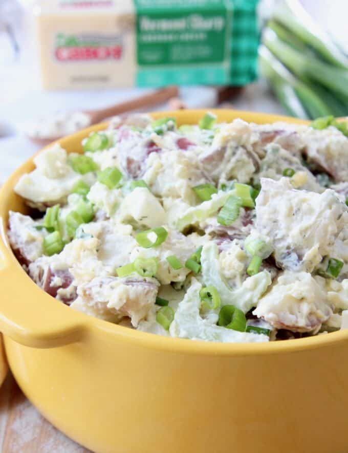 potato salad with celery and green onions in yellow bowl