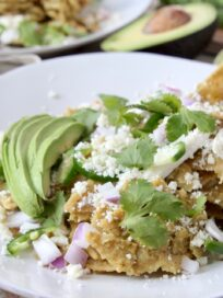 chilaquiles verdes on white plate topped with fresh cilantro and sliced avocado