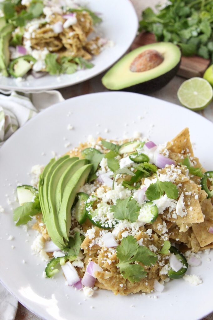 chilaquiles verdes on plate topped with cilantro and cotija cheese