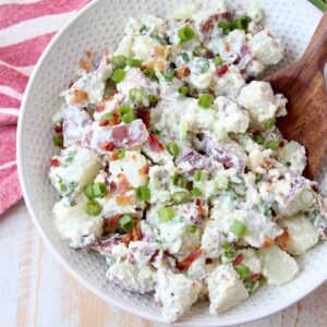 potato salad in white bowl with wooden serving spoon
