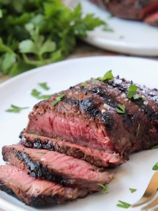 sliced grilled steak on plate with fork