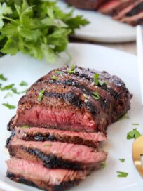 sliced grilled steak on plate, topped with fresh chopped parsley