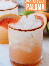 paloma in glass with ice and tajin rim on the glass with a grapefruit wedge