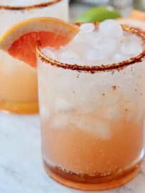 paloma in glass with tajin on the rim and grapefruit wedge on the edge of the glass