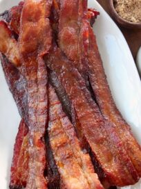 cooked slices of bacon piled up on white plate