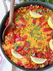 cooked paella in skillet with wooden serving spoon