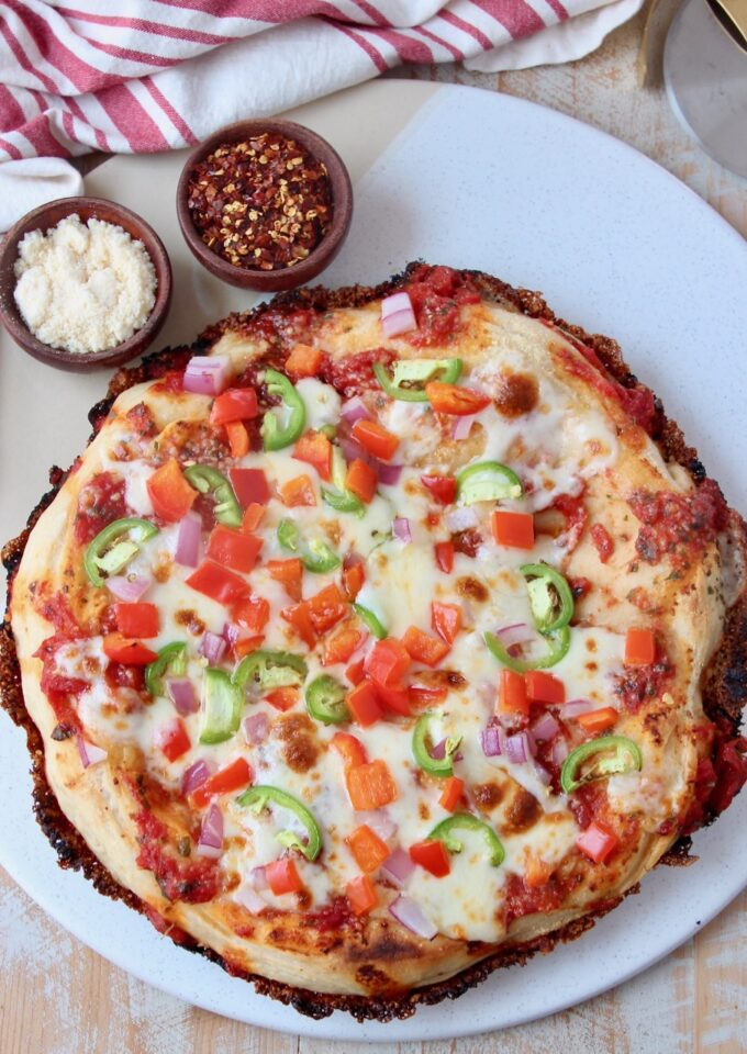 cooked pan pizza topped with veggies on marble serving tray