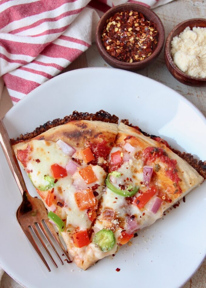 two slices of pizza on white plate with fork