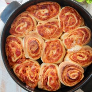 cooked pizza rolls in black baking dish