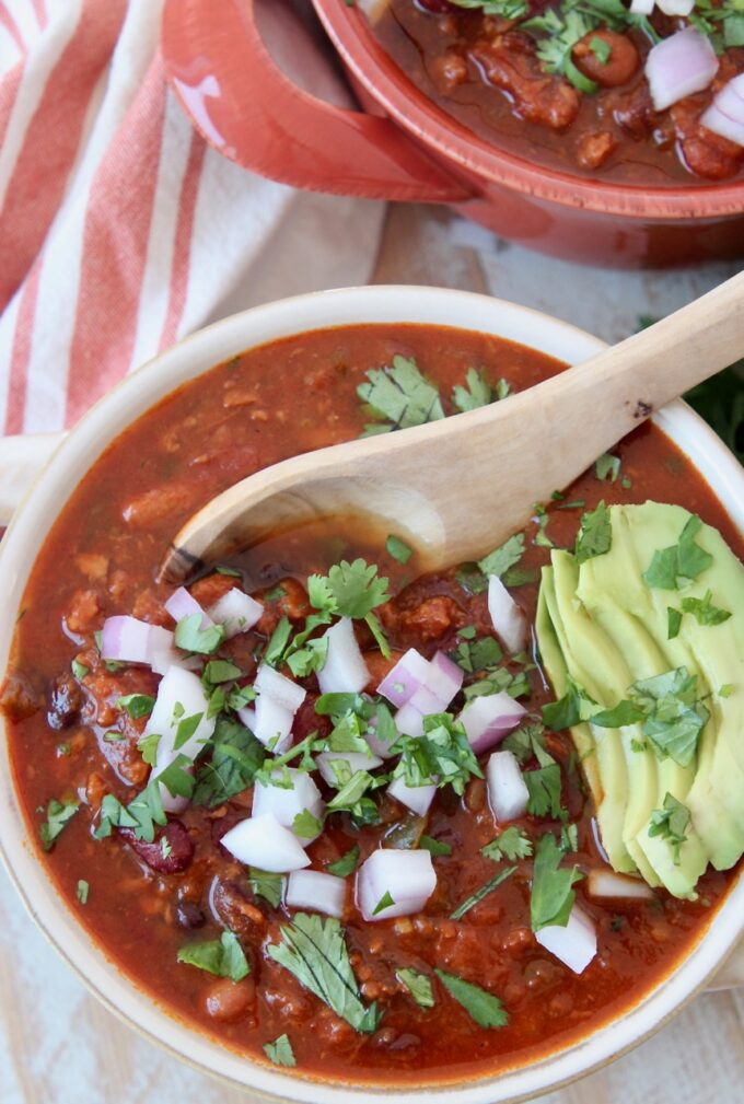 vegan chili in bowl with spoon and sliced avocado