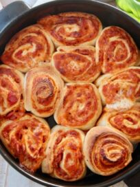 cooked pizza rolls in round black baking dish