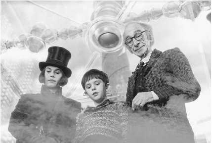 Freddie Highmore as Charlie Bucket (middle) and Johnny Depp as Willy Wonka (left) in a scene from the 2005 movie Charlie and the Chocolate Factory.