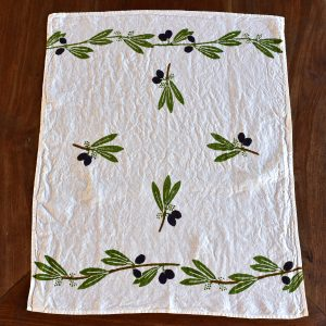 Linen Tea Towel, Block-Printed - Olives. Image displays tea towel laid out across wooden surface.