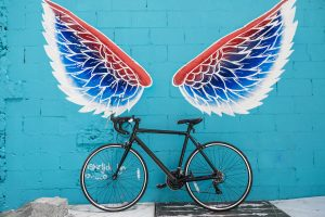 black-road-bike-leaning-on-red-blue-and-white-wing-graffiti-545008
