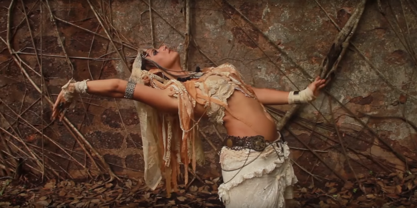 Woman belly dancing in front of the wall