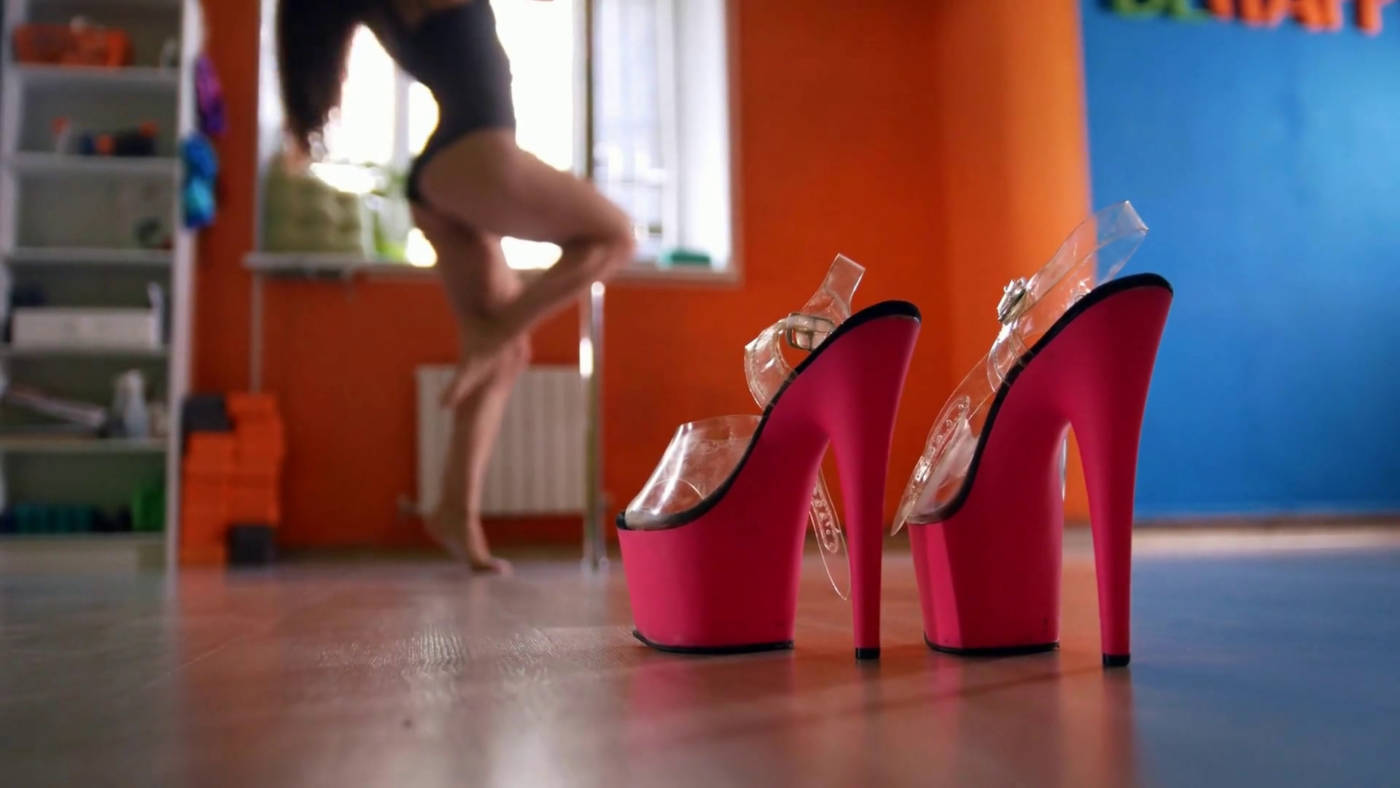 Bright pink dancing dancing shoes with high heels on the front and a girl dancing in the background