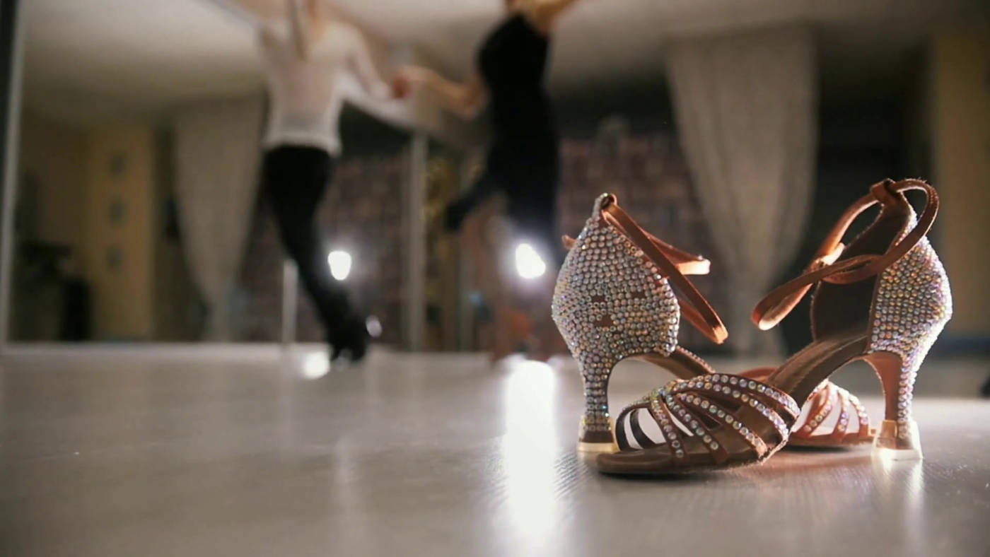 A pair of strappy latin dance shoes in the front a couple of dancers dancing salsa in the background