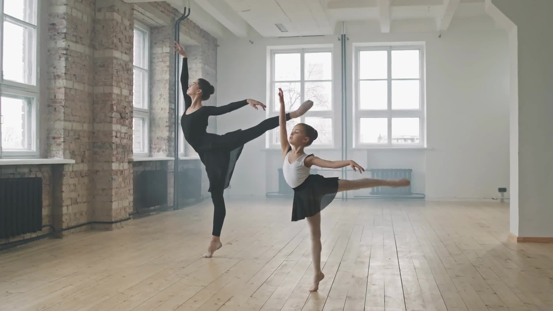 A girl and a woman dancing ballet together in a class