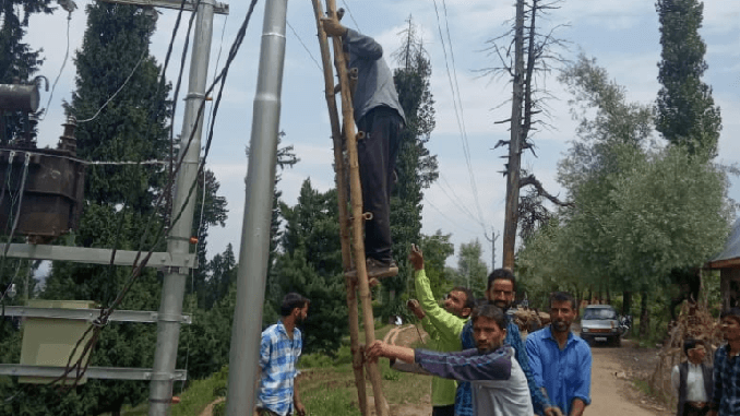 Local people help PDD employees while working on the transmission line