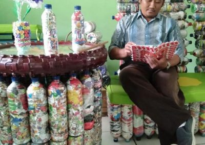 Ood Lantip, reads a book on his Ecobrick courch, beside his ecobrick table in Semarang, Central Java, Indonesia.