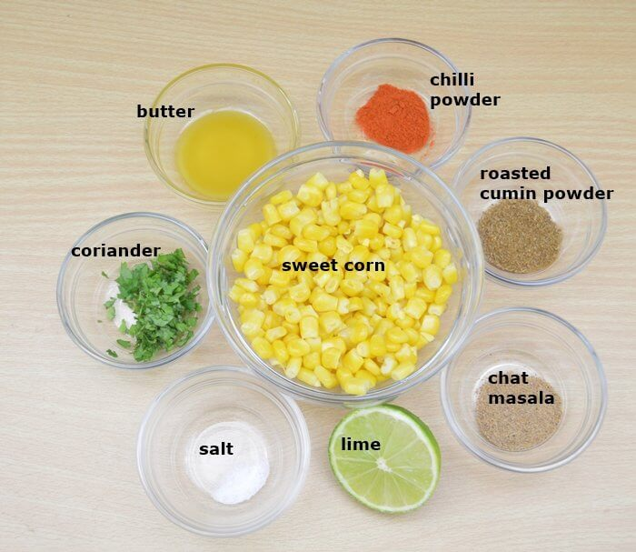 ingredients for masala corn placed in individual bowls on a table.