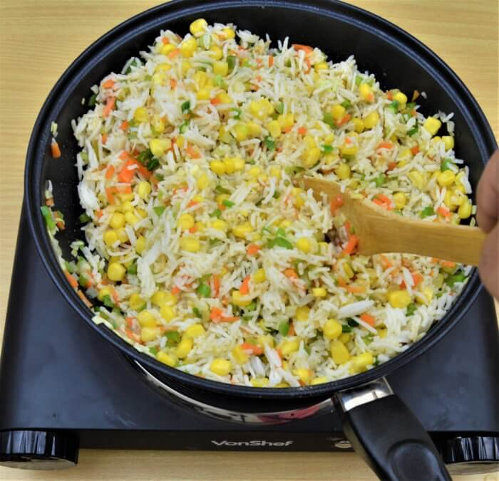 Mixing corn fried rice to blend spices well.