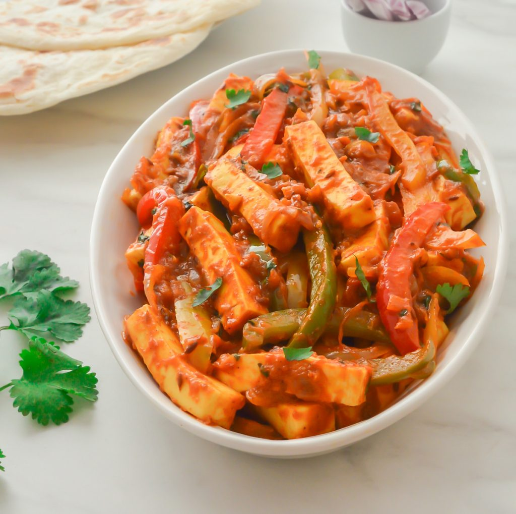 paneer jalfrezi in a white bowl with a paratha, sprig of coriander and onion slices on a marble.