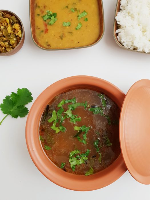 dal rasam in a brown bowl along with rice dal and vegetable fry placed on white table