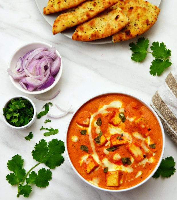 paneer makhani in a bowl with onion slices and coriander in small bowls