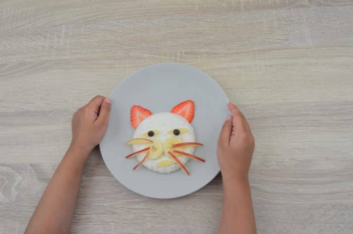 child holding plate of kitty face sandwich