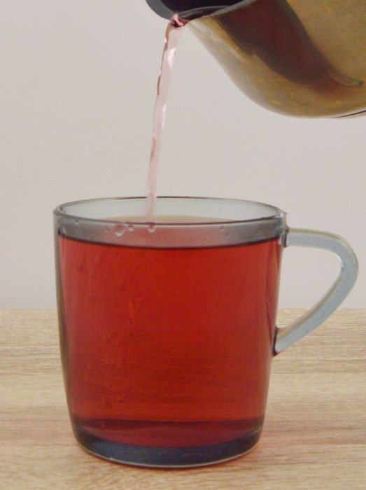 pouring hibiscus tea in a glass.