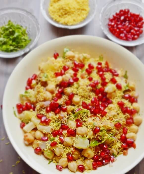 chana chaat in a bowl with coriander, sev and pomegranate in small bowls.