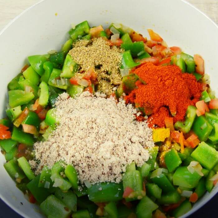 adding dry spices to capsicum curry.