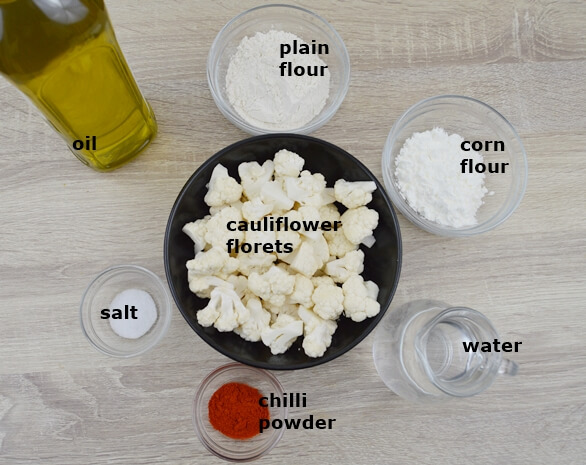 ingredients to make battered cauliflower placed in individual bowls on a table.