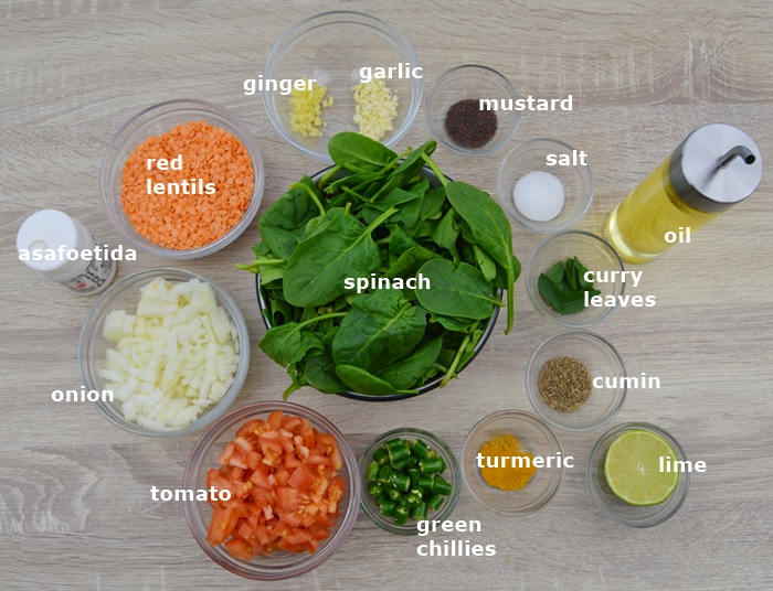 Ingredients to make dal palak placed in individual bowls on table.