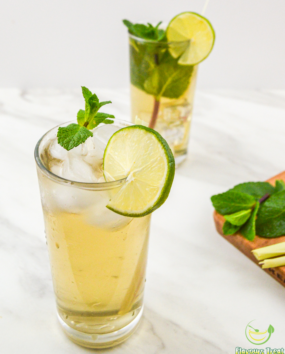 lemongrass ginger iced tea in a tall glass with mint sprig on white table.