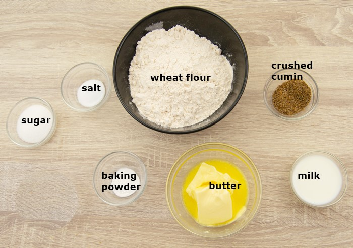 ingredients to make cumin biscuits placed on table.