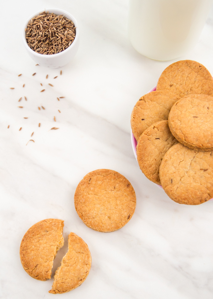 jeera biscuits and a milk places on white table.