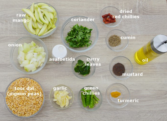 ingredients to make mango dal placed in individual bowls on table.